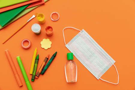 School supplies, medical protective mask blank and sanitizer gel on orange color background, top view, Back to school, coronavirus days. Template, copy space