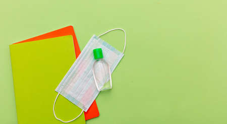 Back to school, coronavirus days. Medical protective mask, hand sanitizer gel and school notebooks on pastel green color background, top view, Template, copy space