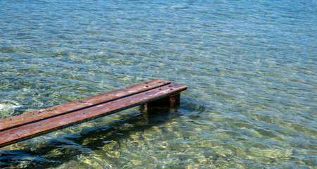 Weathered wooden small pier at Kea, Tzia island, Greece. Wood planks set properly on rusty barrel to make a mini platform over a transparent calm blue sea background.