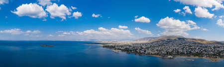 Athens Greece riviera panorama. Aerial drone view of Voula and Glyfada coastline, high class residential distric. Cloudy blue sky over sea water, sunny summer day