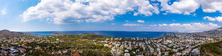 Athens Greece riviera panorama. Aerial drone view of Vouliagmeni and Kavouri coastline, high class residential distric. Cloudy blue sky over sea water, sunny summer day