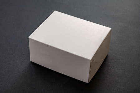 Package box rectangle, blank advertise template for products packaging. White color empty closed cardboard container against black background Foto de archivo
