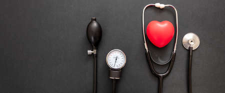 Blood pressure measure equipment, Hypertension control. Medical stethoscope and sphygmomanometer on black color background, top view.