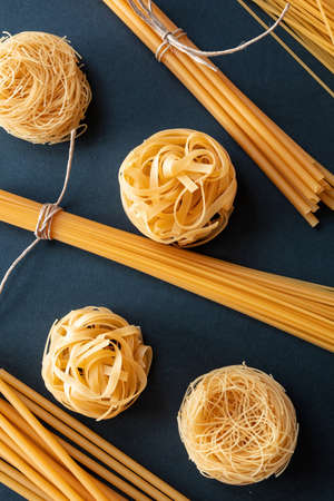 Pasta cooking concept. Raw pasta spaghetti and noodles variety on black background, top view, vertical 免版税图像