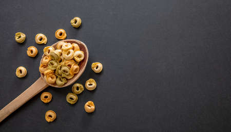 Pasta cooking concept. Fresh homemade tortellini on a wooden spoon, black stone background, top view, copy space 免版税图像