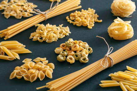 Pasta cooking concept. Raw pasta shapes variety on black background, closeup view