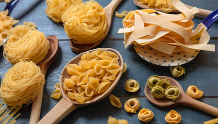 Pasta cooking concept. Raw pasta various shapes and spoons flat lay on blue wooden table background, closeup view