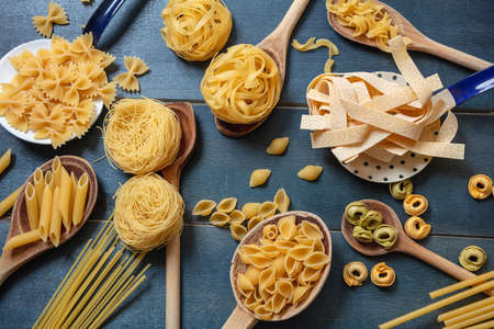 Pasta cooking concept. Raw pasta various shapes and spoons flat lay on blue wooden table background, top view