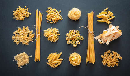 Pasta cooking concept. Raw pasta shapes variety flat lay on black background, top view