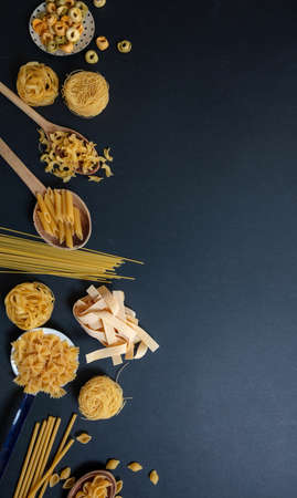 Pasta cooking concept. Raw pasta various shapes and spoons on black stone background, top view 免版税图像