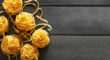 Pasta cooking concept. Raw pasta tagliatelle nests on blue wooden table background, top view, copy space