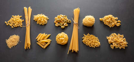 Pasta cooking concept. Raw pasta shapes variety flat lay on black background, top view, banner 免版税图像