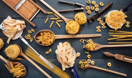 Pasta cooking concept. Raw pasta various shapes and vintage culinary equipment flat lay on blue wooden table background, top view