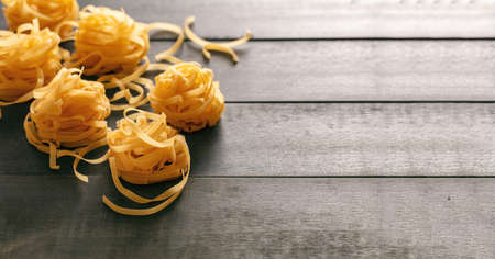 Pasta cooking concept. Raw pasta tagliatelle nests on blue wooden table background, close up view, copy space 免版税图像
