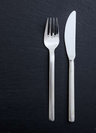Table setting, business lunch. Fork and knife isolated on black background, vertical top view