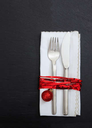 Christmas table setting, holiday lunch dinner. Cutlery, white linen napkin and red xmas decoration isolated on black background, vertical top view
