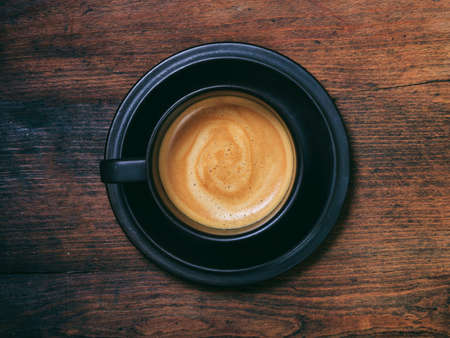Coffee time. A cup of espresso coffee on wooden table background, top view