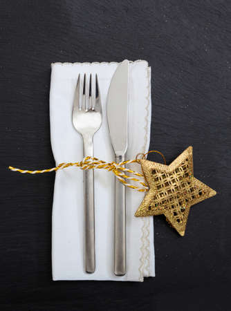 Christmas table setting, holiday lunch dinner. Cutlery, white linen napkin and golden xmas decoration isolated on black background, vertical top view 免版税图像