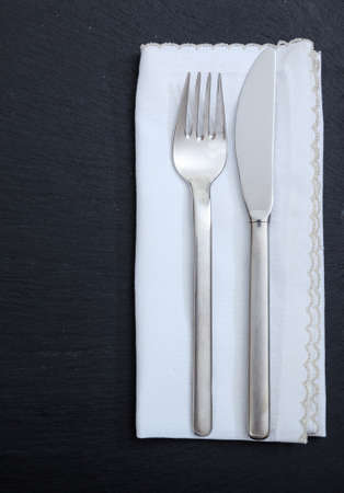 Table setting, business lunch. Fork knife and white linen napkin isolated on black background, vertical top view