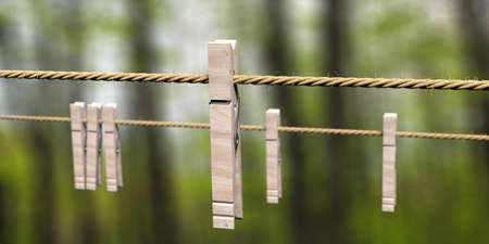 Clothespins on clothes rope against blur green nature background. Laundy drying retro tools, pegs for clothes hanging. 3d illustration