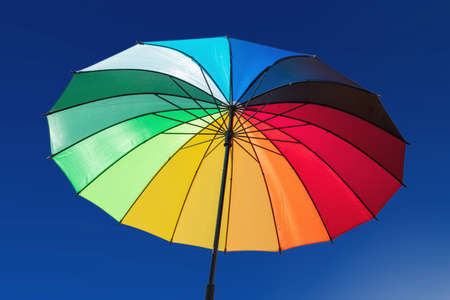 Rainbow colors umbrella against blue sky background, sunny day. Gay pride, freedom symbol