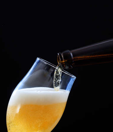 Beer bottle pouring golden ale beer in a glass, black backgrounnd, closeup cropped portrait view, copy space