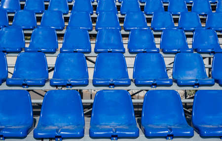 Stadium seats background. Rows of blue plastic empty seats. Sports or concerts audience chairs