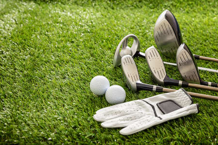 Golf equipment, sticks set, glove and golfballs on green course lawn, close up view. Golfing sport and club concept