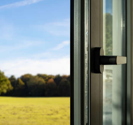 Aluminum door detail. Metal window frame open closeup view. Energy efficient, safety profile, blur outdoor nature background