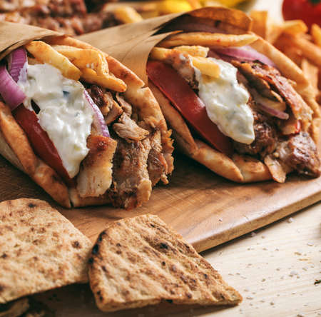 Gyros wraps greek food. Grilled meat sliced with fried potatoes, tomato and yogurt tzatziki in a pita bread, wooden table background, closeup view. Turkish shawarma Stockfoto