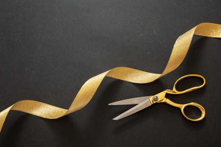 Grand opening. Gold scissors and golden silk ribbon, black background, top view. Invitation template, copy space