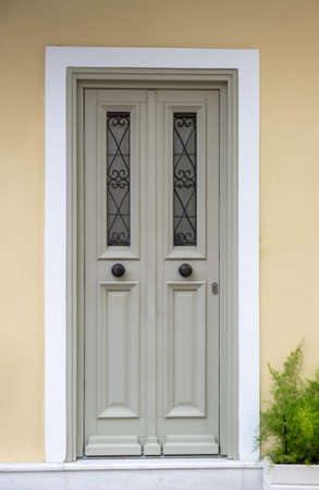 Wooden entrance door, beige yellow color wall background, residential building in old town of Plaka, Athens Greece 版權商用圖片