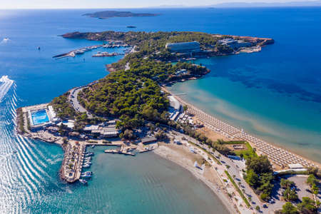 Athens Riviera, south coast, Greece. Asteras Vouliagmeni luxury resort hotel aerial drone view. Transparent turquoise sea water and sandy beach, sunny summer day.