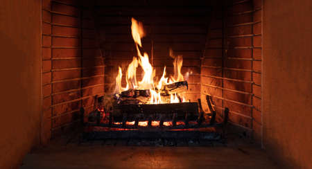 Fireplace, cozy warm fireside. Fire burning, logs flaming, firebricks background. Relaxation at home winter holiday christmas time Imagens