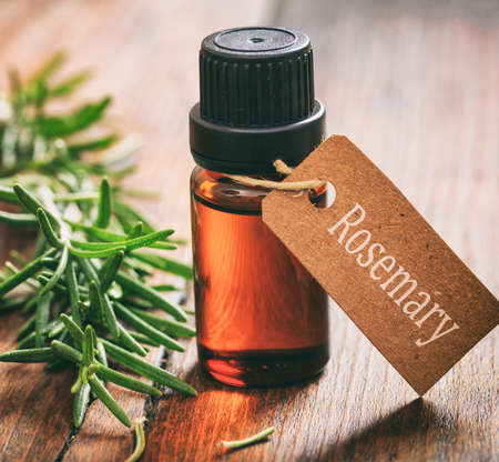 Rosemary essential oil and fresh leaves on wooden background. Salvia rosmarinus is a woody, perennial herb with fragrant, evergreen, needle like leaves