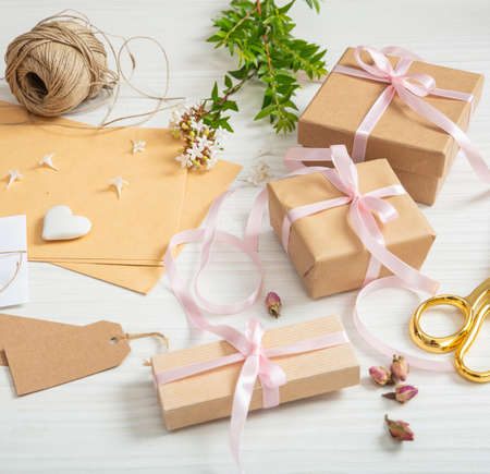 Gift boxes and invitations flat lay on white wooden tabletop. Above view of handmade present packages, blank brown tags, kraft wrapping paper, pink ribbon background. Ideal for celebration, event.
