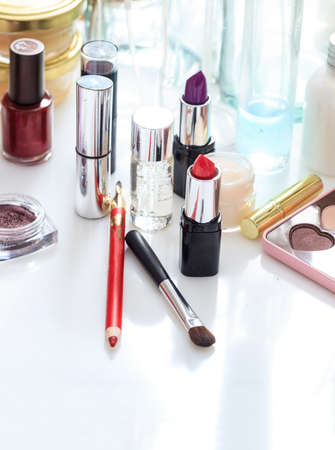 Makeup cosmetics set on white background. Cosmetology industry creates luxury collection for skincare, fashion, beauty and protection of woman face and nails. Vertical, close up view.
