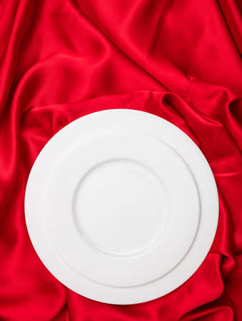 Valentines dinner concept. Vertical top view of empty set white plates on red satin background. Formal blank dishware on silk cloth passion red color for wedding proposal on valentine day. Copy space.