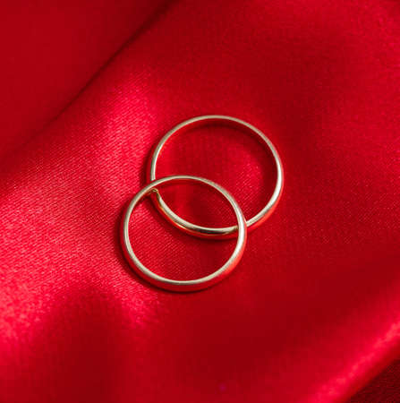 Wedding rings concept. Top view marriage, engagement golden rings on red satin background. Jewelries for couple in love on silk cloth passion red color for romantic wedding proposal on valentine day.