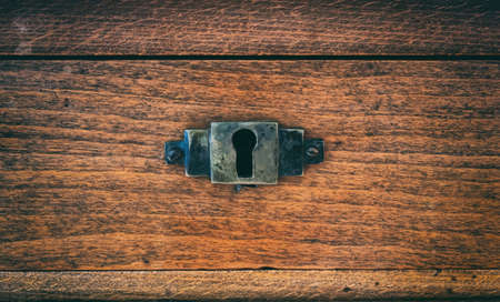 Secret, mystery concept. Close up view of peeled old-fashioned keyhole on wooden background. Metal hole aged lock, safety protection