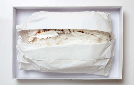 Christmas stollen cake Christstollen isolated on white. Sweet german traditional bread wraped with paper in a carton box, top view. Xmas gift from Dresden