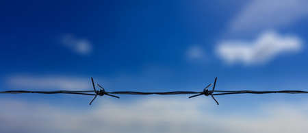 Barbed wire on blue cloudy sky background, Close up view of horizontal metal barb wire. Military area, prison, security barrier or freedom concept.