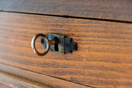 Secret, mystery privacy concept. Retro key on an old fashioned keyhole, wooden drawer background close up view. Vintage furniture detail