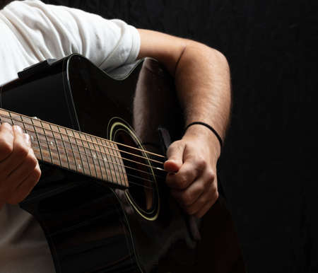 Entertainment concept. Young man playing acoustic guitar, dark background. Guitarist in casual white shirt holds electric black instrument at studio.