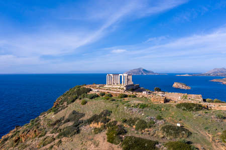 Greece Cape Sounio, Poseidon temple aerial drone view. Archaeological site of ancient greek temple ruins up on a hill, Athens Attica. Cloudy blue sky backgrpund, sunny day