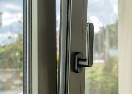 Metal or PVC window vertical open closeup view. Tilt and turn grey color aluminum window, fresh air for home. Energy efficient, security profile metal door frame.