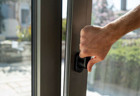 Tilt and turn grey color aluminum window, man holding the handle, fresh air for home. Male hand vertical open metal or PVC window, closeup view.