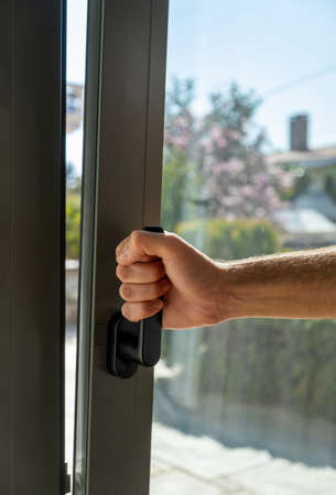 Male hand open metal or PVC window, vertical closeup view. Tilt and turn grey color aluminum window, man holding the handle, fresh air for home.