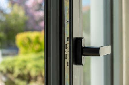 Metal or PVC door open detail. Aluminum window frame closeup view. Energy efficient, safety profile, blur garden outdoor background