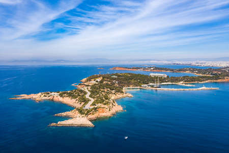 Athens Greece riviera coast, Vouliagmeni, panoramic aerial drone view of the bay and peninsula, south coast. Cloudy blue sky, calm sea water Imagens